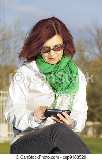 Good looking mid age woman with tab - csp9183520