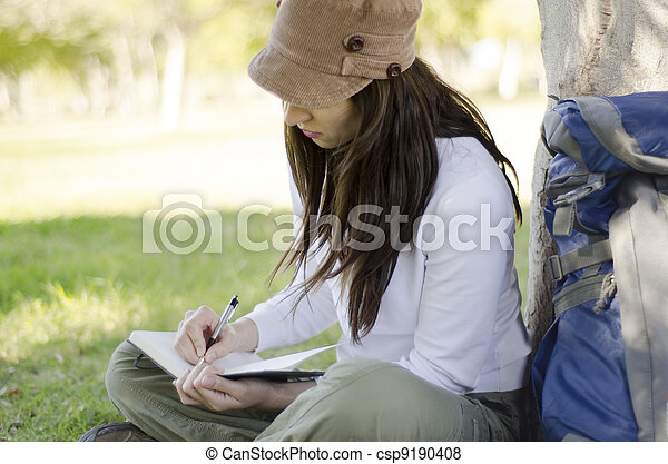 Woman writing on travel journal - csp9190408