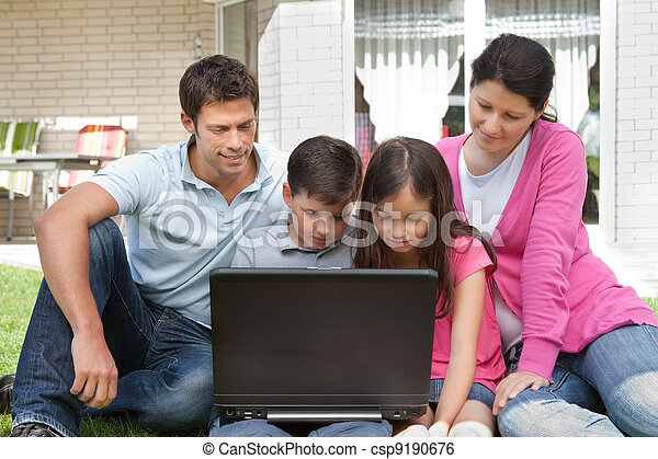 Young family in backyard using laptop - csp9190676