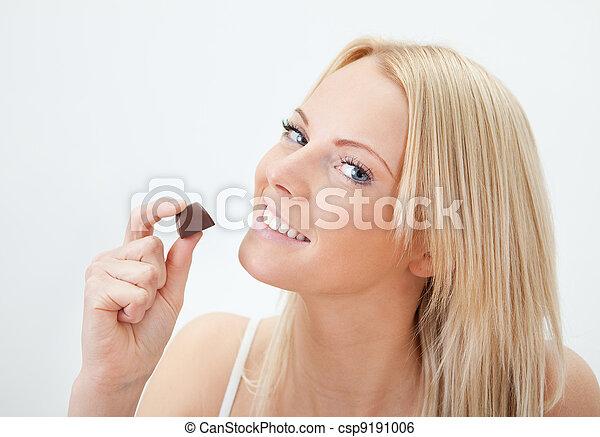 Beautiful woman eating chocolate - csp9191006