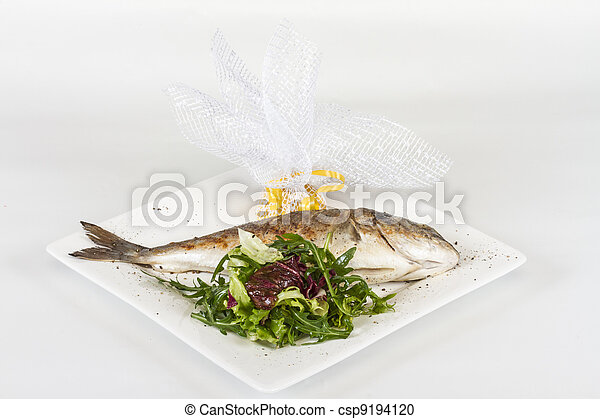 Dorada fish with salad on the white plate. Studio shot - csp9194120