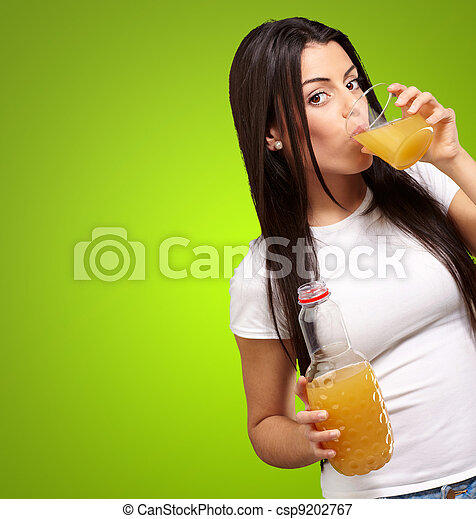 portrait of young girl drinking orange juice against a green background - csp9202767