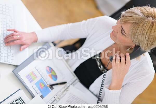 Mature business woman making phone call. Top view - csp9205256