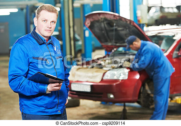 happy mechanic technician at service station - csp9209114