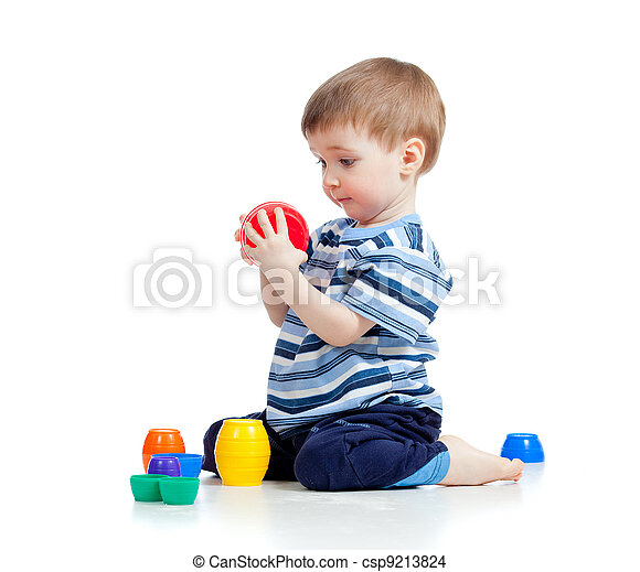 Cute little child is playing with toys while sitting on floor, isolated over white - csp9213824