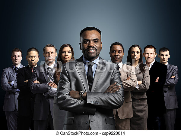 business team formed of young businessmen standing over a dark background - csp9220014