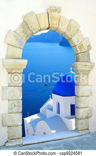 Traditional greek church  through an old window in Santorini island, Greece - csp9224581
