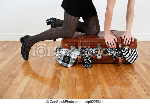 Woman packing overfilled suitcase - csp9225614