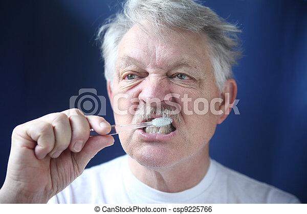mature man brushes teeth - csp9225766
