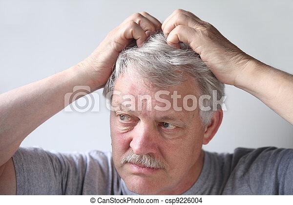 senior scratches his head - csp9226004