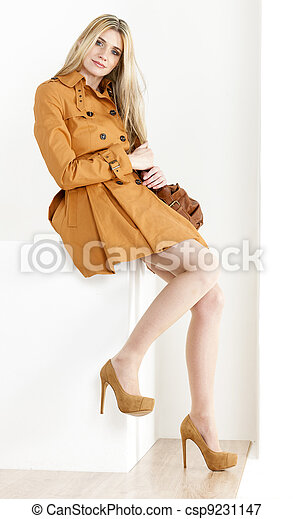 sitting woman wearing brown coat and pumps with a handbag - csp9231147