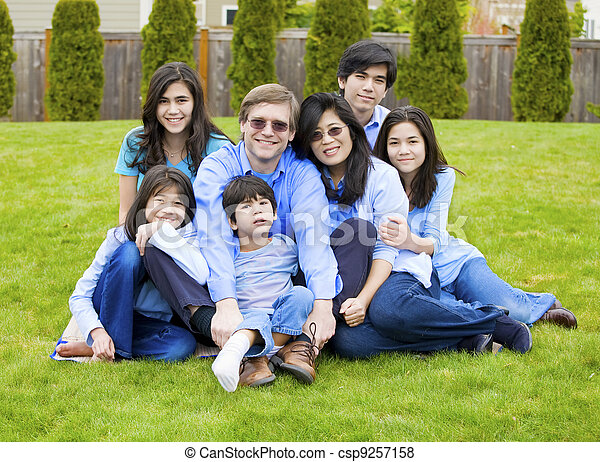 Large multiracial family of seven sitting together on lawn, dressed in blue colors. Five year old boy in front is disabled with cerebral palsy. - csp9257158