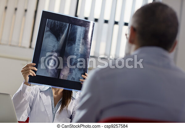 Female doctor working in hospital with patient and x-rays - csp9257584