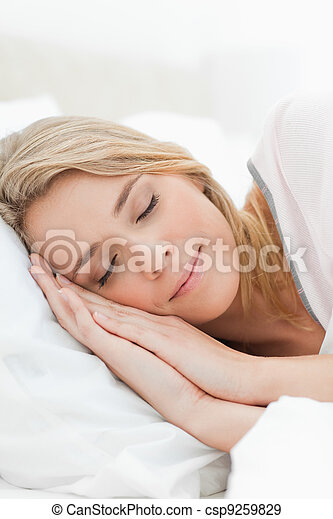 A close up shot of a woman resting in bed with her hands pressed on the pillow beside her head. - csp9259829