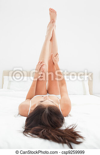 A close up shot of a woman with her legs raised fully upwards with her arms about half way up the length of her legs. - csp9259999