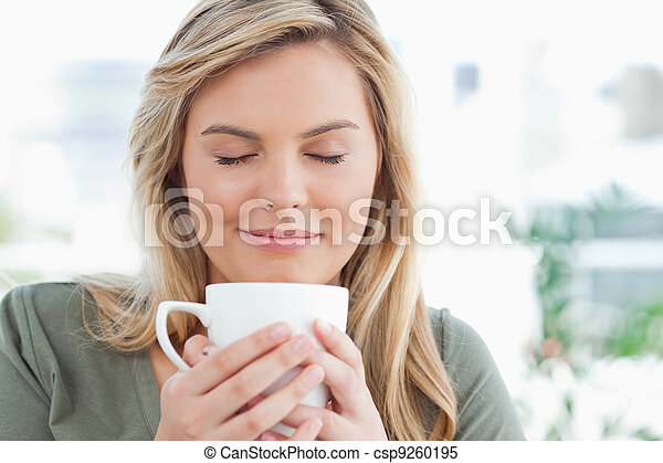 A woman with a soft smile and closed eyes, smelling the aroma from her cup in front of her. - csp9260195