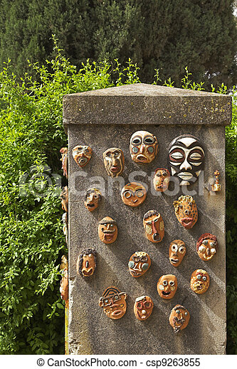 The curbstone in a garden, decorated ceramic ritual masks - csp9263855