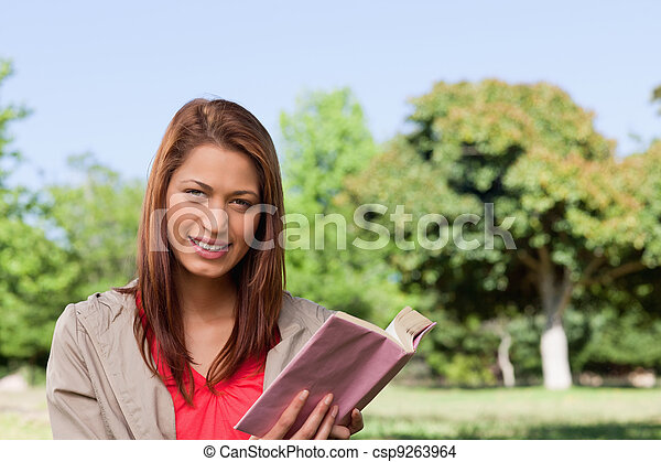 Woman grinning while looking straight ahead with a book in her hands in a sunny grassland area - csp9263964