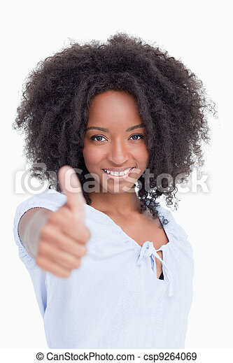 Woman smiling and standing upright while placing her thumbs up in satisfaction - csp9264069