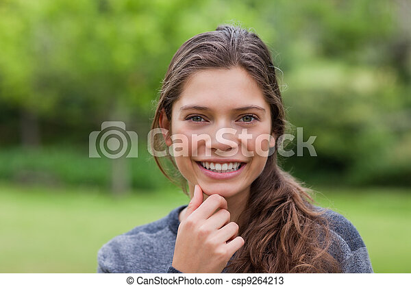 Smiling young adult placing her hand on her chin while standing up in the countryside - csp9264213