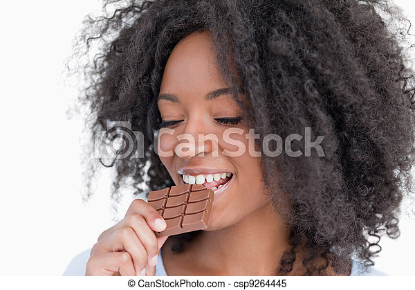 Young woman eating a delicious piece of chocolate bar - csp9264445