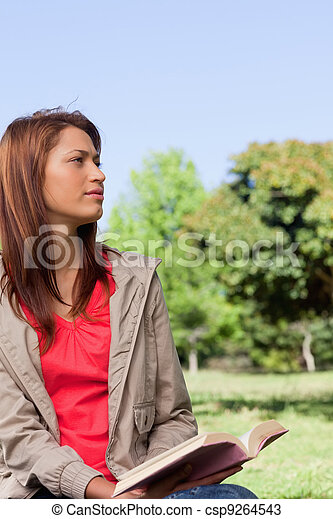 Young woman looking into the distance while sitting down with a book in her hands - csp9264543
