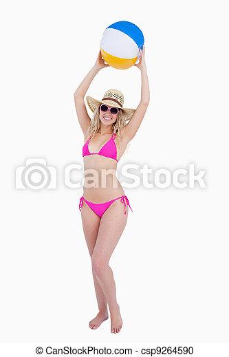 Smiling attractive teenage in beachwear raising a beach ball above her head - csp9264590