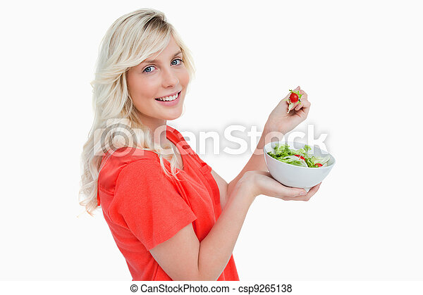 Side view of a young woman showing a great smile while eating sa - csp9265138