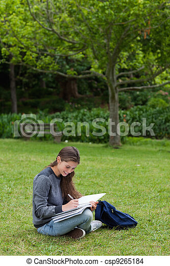 Smiling young adult seriously writing on her notebook while sitting down in a park - csp9265184