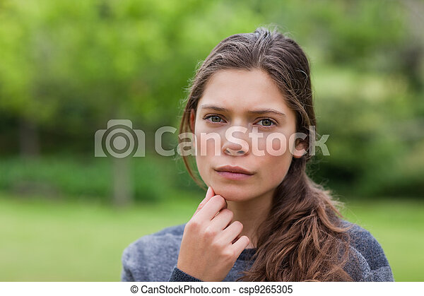 Young thoughtful adult looking at the camera while placing her hand on chin - csp9265305