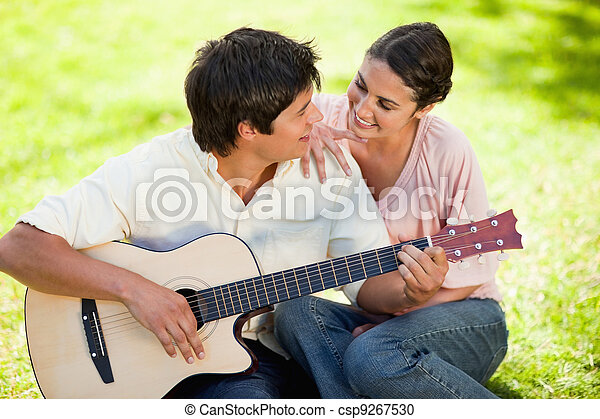Man plays the guitar while looking at his friend who has her hand on his shoulder as they both sit on the grass - csp9267530
