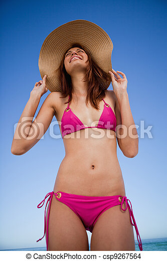 Low-angle view of a smiling teenager wearing a pink swimsuit - csp9267564