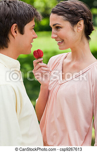 Woman laughing while offering a strawberry to her friend - csp9267613