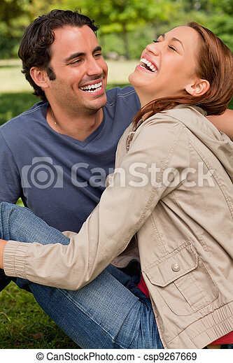 Two friends gleefully laughing as they are sitting next to each other on the ground in a shaded area of a park - csp9267669