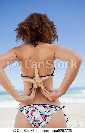 Young woman in swimsuit holding a starfish on her back - csp9267728