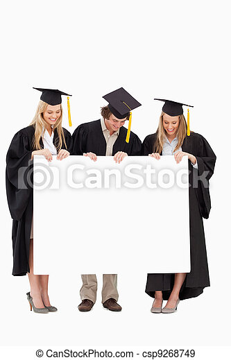 Three smiling students in graduate robe holding a blank sign - csp9268749