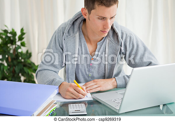 Student doing his homework with a laptop - csp9269319