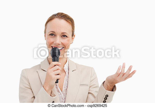 Pretty woman in a suit speaking with a microphone  - csp9269425