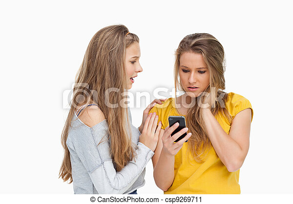 Upset young woman holding her cellphone consolded by her friend - csp9269711