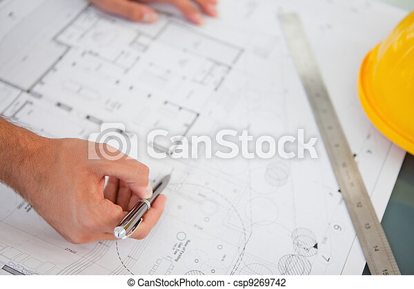 Close up of blueprints with a person making adjustments - csp9269742