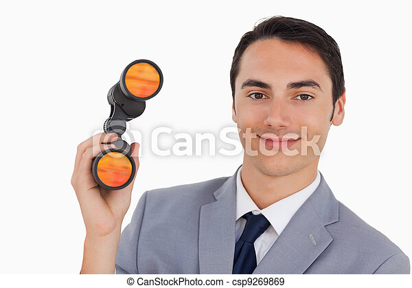 Close-up of a smiling businessman with binoculars  - csp9269869