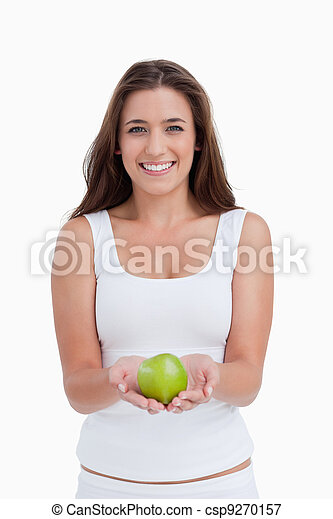 Smiling woman looking at the camera while holding an apple - csp9270157