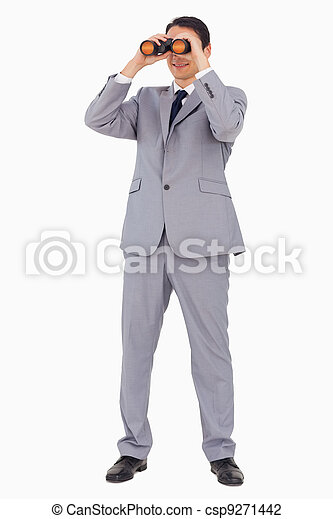 Businessman smiling while using binoculars  - csp9271442