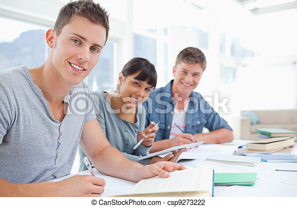 A side view shot of a group of young adults with their homework on the table as they all look into the camera - csp9273222