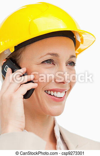 Close-up of a woman wearing safety helmet on the phone - csp9273301