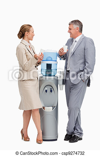 Business people talking next to the water dispenser  - csp9274732