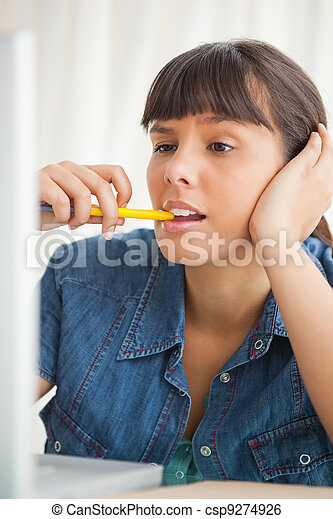 Student grimacing while chewing a pencil - csp9274926