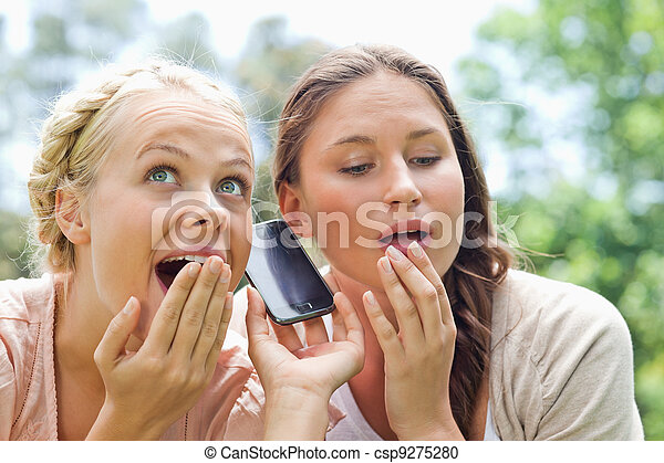 Curious friends listening to phone call in the park - csp9275280