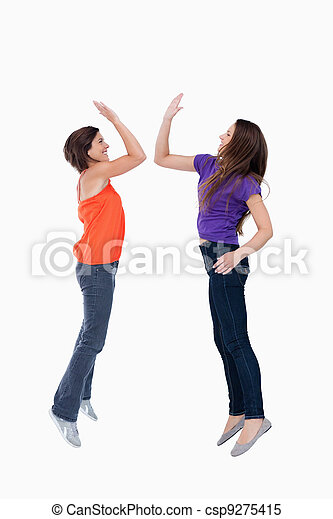 Two teenagers which are giving a high-five while jumping - csp9275415