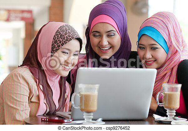 young muslim woman in head scarf using laptop in cafe with friends - csp9276452